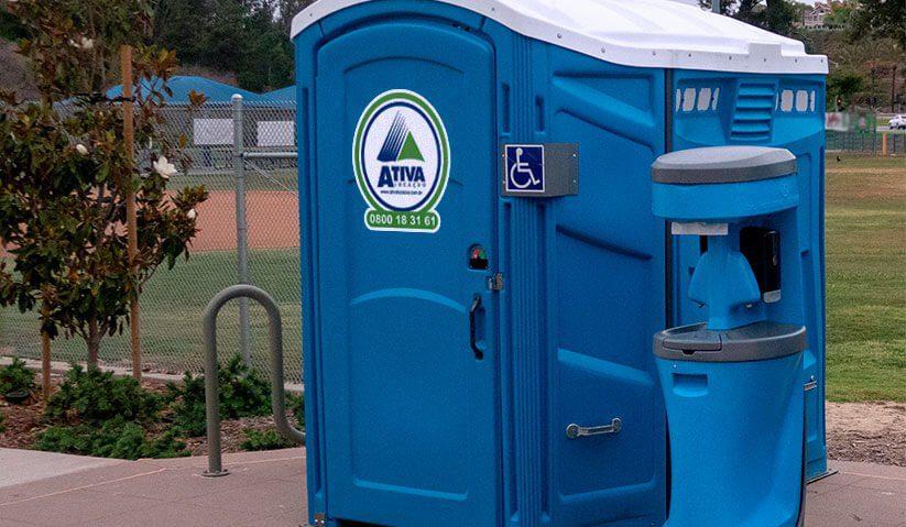 Imagem de um toalete portátil PcD Ativa instalado junto a um lavatório portátil.
